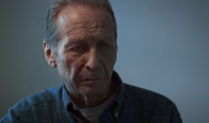 Paul Raci in the film Sound of Metal. He's wearing a blue flannel shirt and looks gravely concerned.