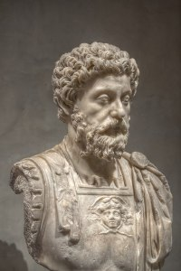 Statue of Marcus Aurelius at the Musee Saint-Raymond. Aurelius has short, curly hair and a full beard. He's also wearing Roman legionnaire armor.